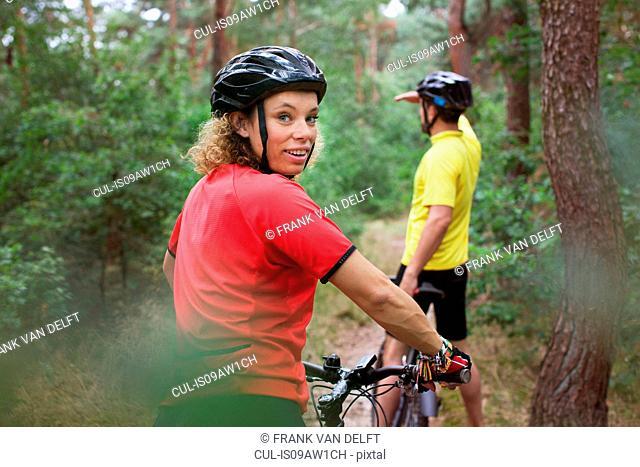 Mountain biking couple biking on forest trail