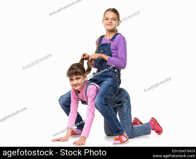 Girl sits on top of another girl like a horse