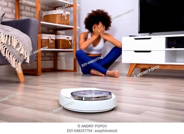 Weighing Scale In Front Of Crying Young Woman Sitting In The Living Room