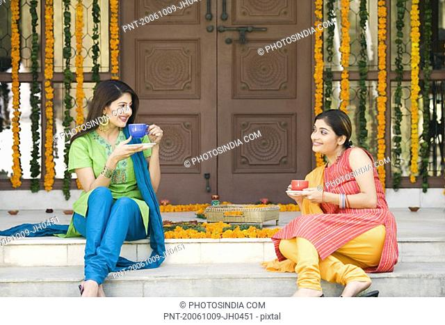 Two young women sitting at doorstep of a house and holding cups of tea
