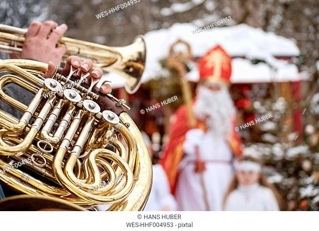 Musician playing horn with angel and Santa Claus in background