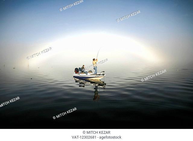 Fisherman In Boat On Water