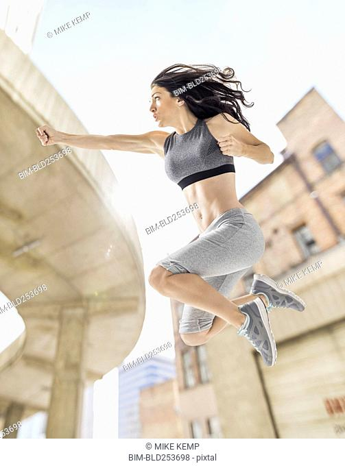 Caucasian woman jumping and punching in city