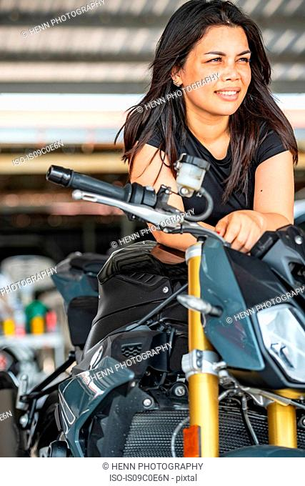 Female motorcyclist leaning on her motorbike at race track, portrait, Bangkok