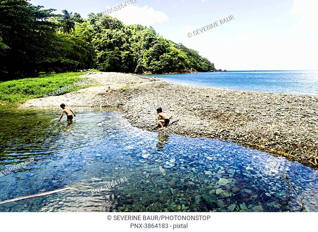 Two kids 6 and 8 years old playing in the river cloth to the sea, Charlotteville, Tobago, Trinidad and Tobago, West Indies, South America