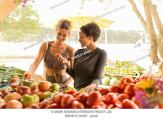 Women browsing produce at farmers market