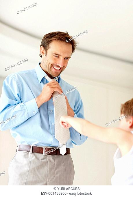 Portrait of a happy young man getting ready for office and a small boy pointing at his necktie