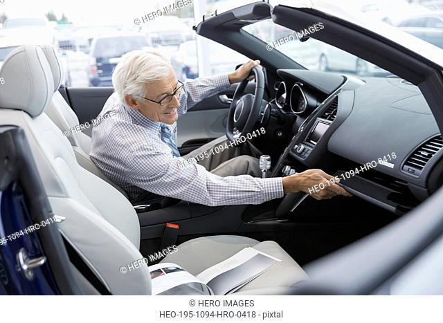 Man looking inside convertible in car dealership showroom