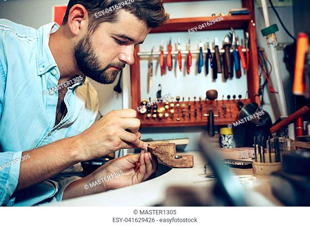 Different goldsmiths tools on the jewelry workplace. Jeweler at work in jewelry. Desktop for craft jewelry making with professional tools