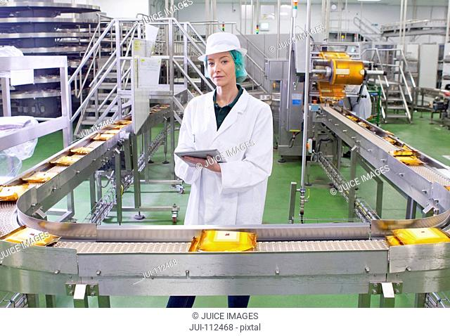 Portrait quality control worker with digital tablet at production line in cheese processing plant