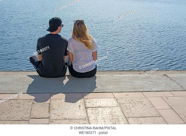 Young couple sit in sunshine watch water glitter on stone pier on a spring day in Mallorca, Spain
