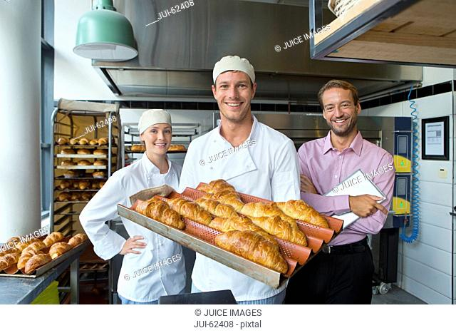Business owner and bakers in bakery kitchen with bread