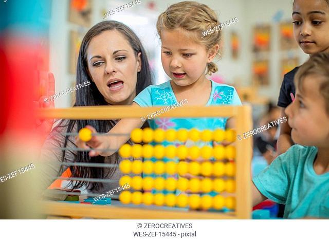 Pre-school teacher with children in kindergarten using abacus
