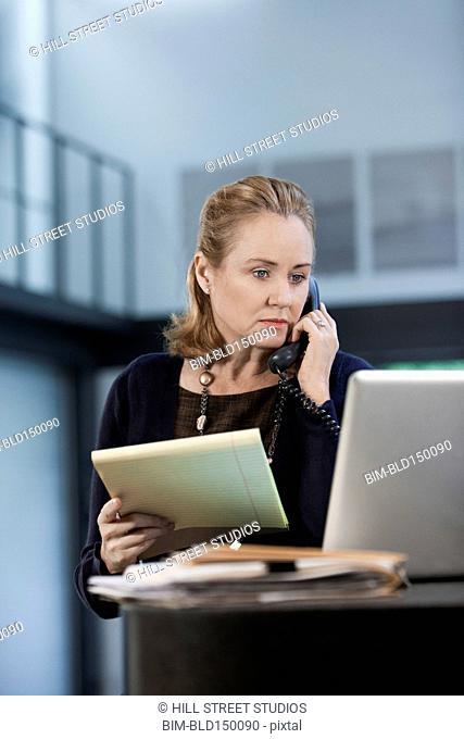 Caucasian businesswoman talking on telephone