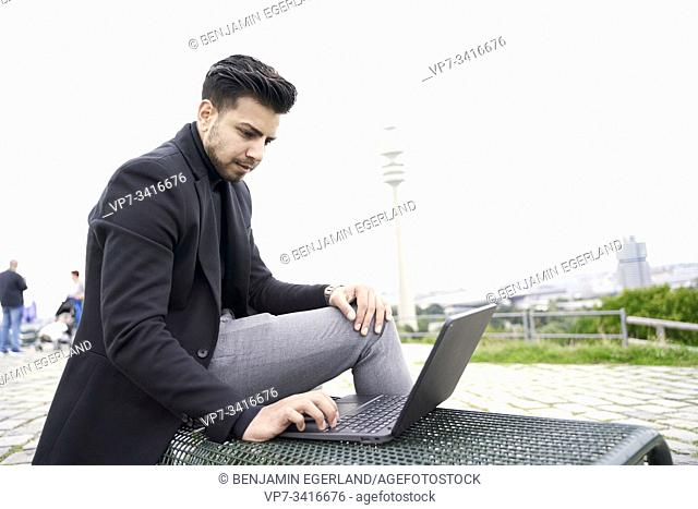 Young Asian man using mobile laptop computer with good wireless internet connection thanks to radio mast on Olympiaberg in Olympiapark in Munich, Germany