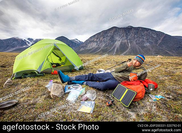 Climber eats meal, relaxes, charges devices at campsite