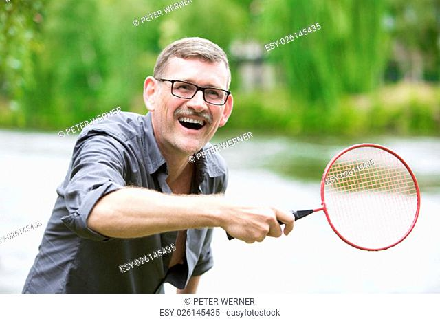 man is playing badminton by the water