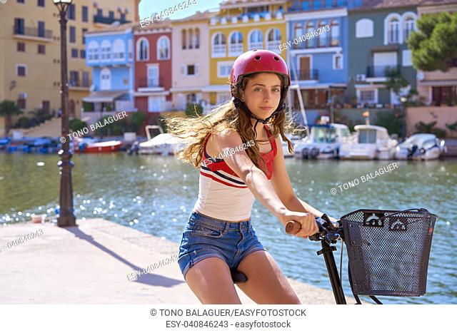 Girl riding a foldable e-bike in a Mediterranean marina port ebike