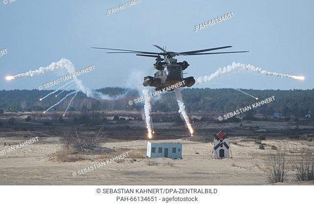 A CH-53 GS helicopter shooting flares during a training exercise at the Oberlausitz military training area near Weisskeissel, Germany, 24 February 2016