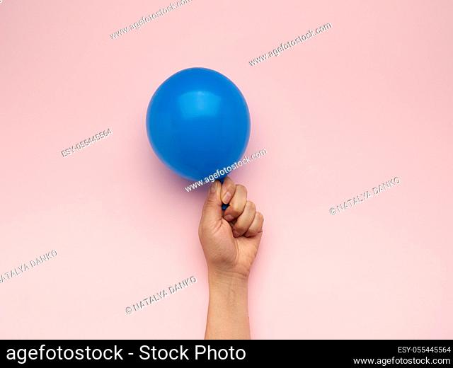 female hand holding an inflated blue air balloon on a pink background, close up
