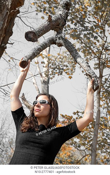 Young woman, wearing sunglasses, holding onto tree branches