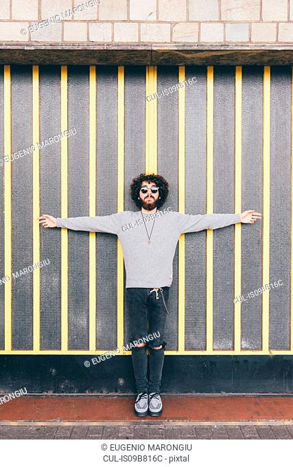 Portrait of young man, arms outstretched, in urban environment