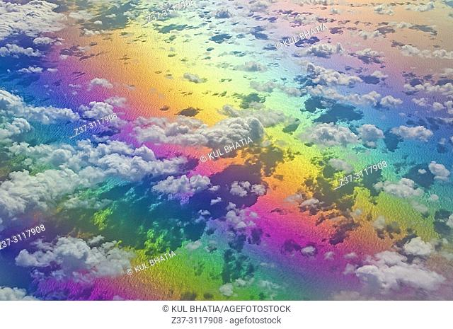 Aerial view of clouds below, at 10,000 meters, photographed from a regular commercial flight. The rainbow of colours is due to light refraction