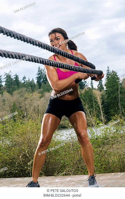 Mixed Race woman working out with heavy ropes