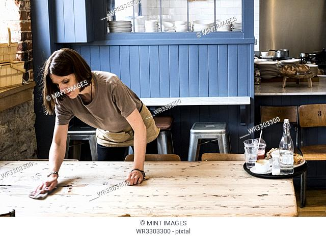 A female waitress clearing a table and wiping it in a cafe