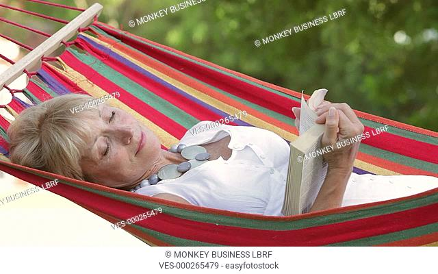 Senior woman rocking in hammock turning pages of book. Shot on Canon 5d Mk2 with a frame rate of 30fps