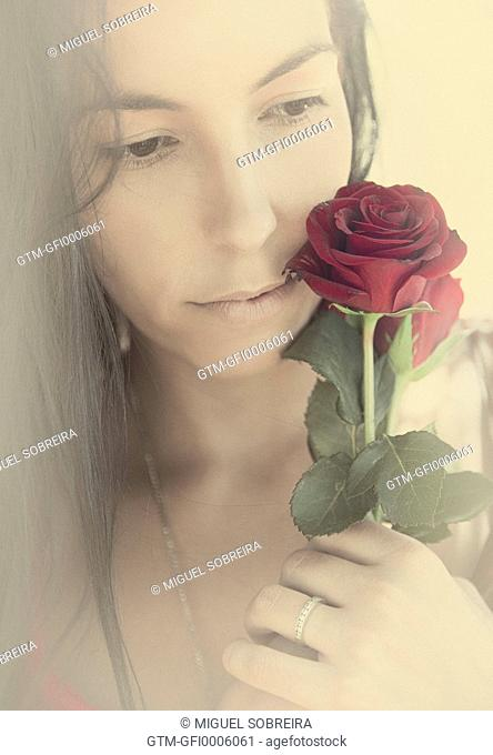 Woman Holding Rose Against Skin