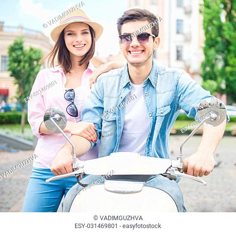 Beautiful young couple smiling to camera while man sitting on scooter. Fun time together