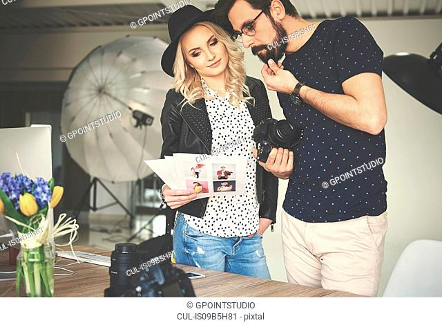 Photographer and stylist looking at photographs in photography studio