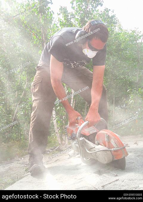 Geologist taking a channel sample from a rock outcrop with a circular hand saw. Sun beams get visible in the dust