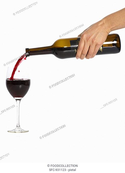 Woman's hand pouring red wine