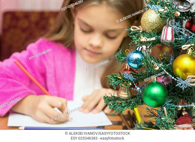 Christmas Tree in the foreground, in the background a girl writing a letter