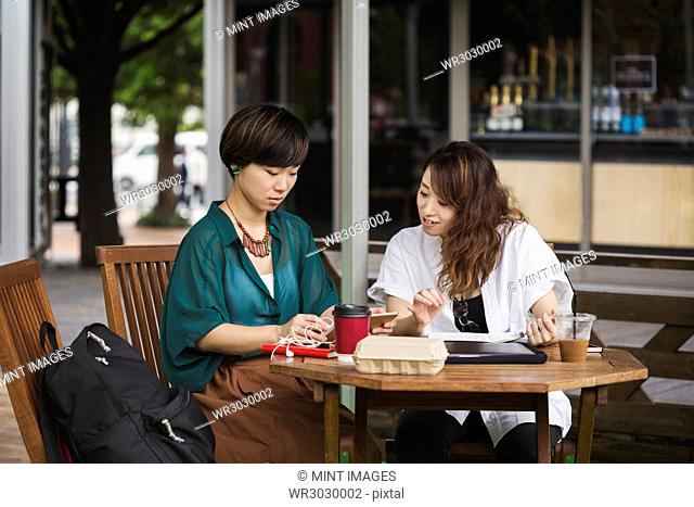 Two women with black hair wearing green and white shirt sitting at table in a street cafe, looking at digital tablet