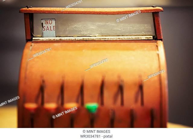 A retro style bronze coloured cash register, an old fashioned till with keys and a glass display