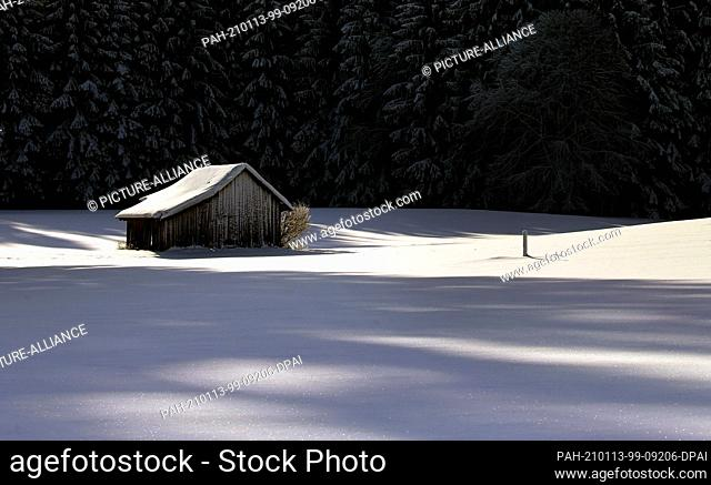 13 January 2021, Bavaria, Rettenbach: A wooden hut stands at the edge of a forest in the deep snow-covered landscape. Photo: Karl-Josef Hildenbrand/dpa