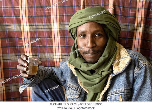 Tripoli, Libya - Ali, a Tuareg Tailor, Stops for Tea in Tripoli Medina Old City  His dress combines traditional male veil tagulmust with Western denim jacket