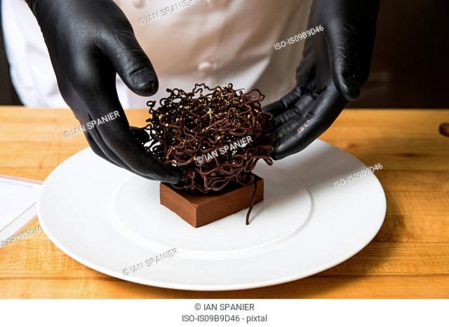 Chef placing chocolate nest cake decoration on cake