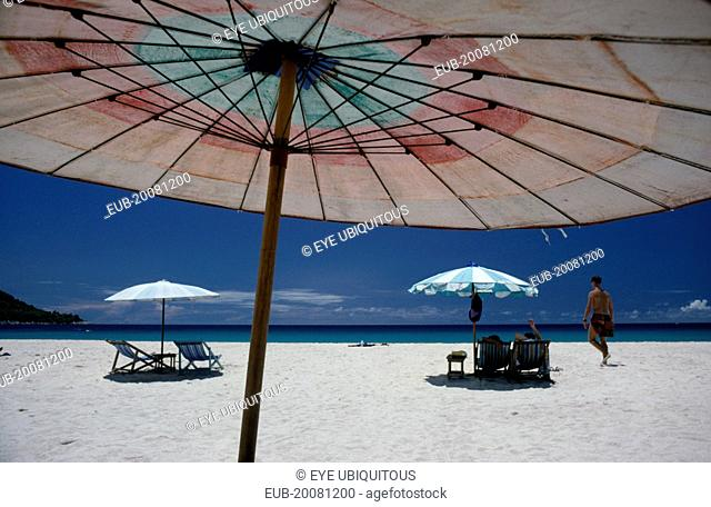 Western tourists on white sand beach with sun loungers part framed by umbrella in the foreground