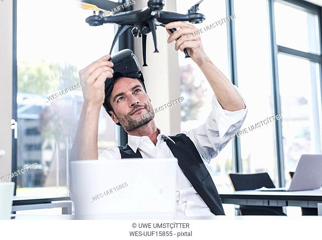 Businessman sitting in office working on a drone, using VR glasses