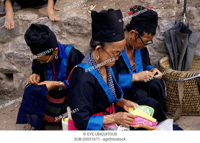 Hmong women in traditional dress doing embroidery