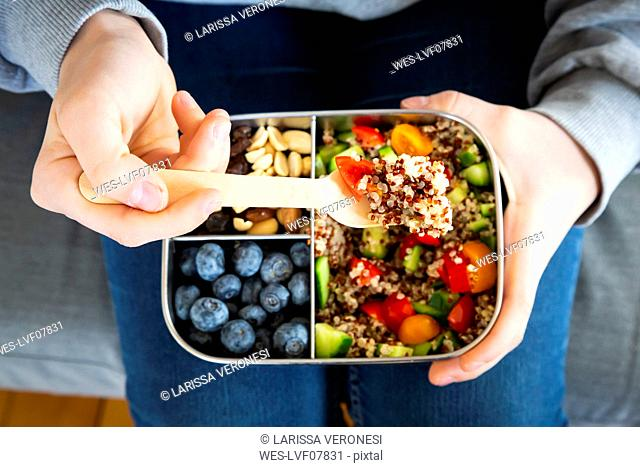 Lunchbox with quinoa salad with tomato and cucumber, blue berry and trail mix