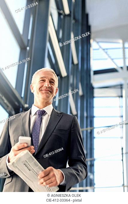 Smiling businessman with cell phone and newspaper in airport