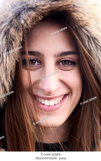 Portrait of happy young woman wearing fur hood