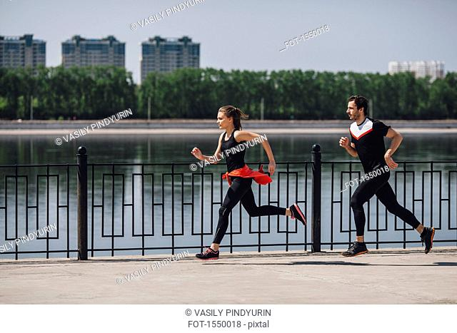Side view of people running on promenade next to lake