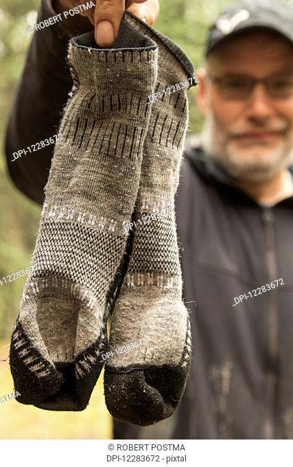 Man holding up his smelly socks after a two week canoe trip down the Wind River; Yukon, Canada