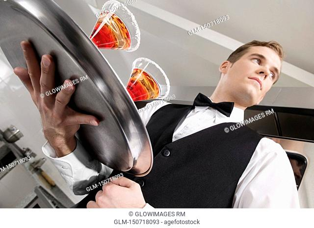 Waiter holding a tray of martini